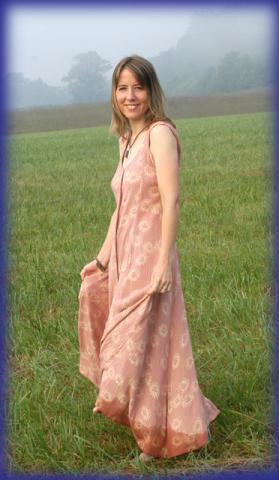 photo of Julie Rust wearing a long, sleeveless summer dress and standing in a field