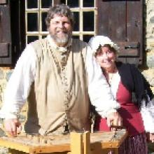 photo of John and Jan Haigis standing outside by a split-rail fence on a sunny day, wearing pioneer costumes