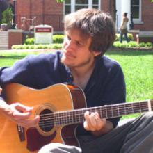 photo of Jon Watts sitting on the grass on a sunny day, playing guitar and singing