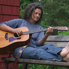 photo of Sara Thomsen sitting outside playing guitar