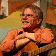 photo of Gordon Bok smiling and seated with his guitar on his lap