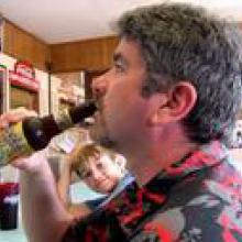 photo of Joe Fahey drinking a bottle of beer at a bar