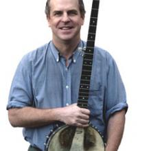 photo of Tom Rawson holding his banjo and smiling